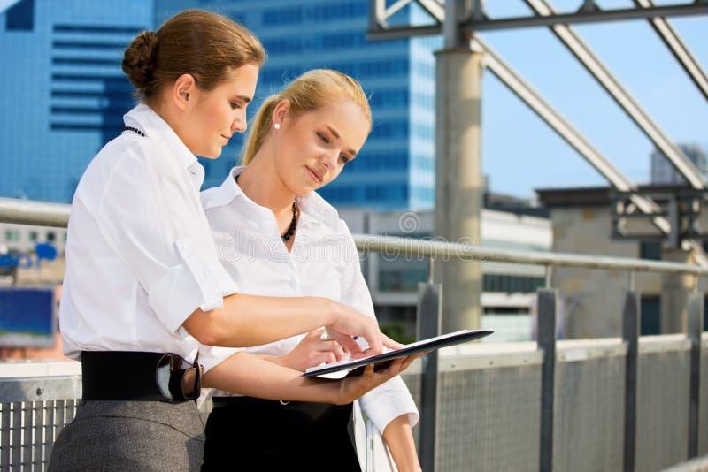 Zwei Geschäftsfrauen mit Papierdiagramm lizenzfreie stockbilder