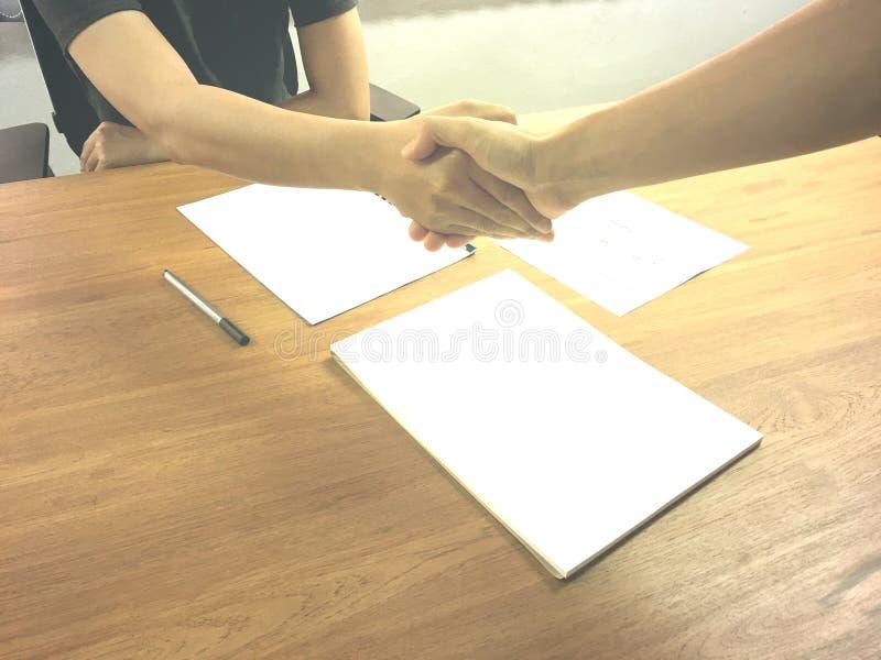Zwei Geschäftsleute übergeben das Rütteln am Arbeitsplatz für Zusammenarbeit zwischen Unternehmen lizenzfreie stockbilder
