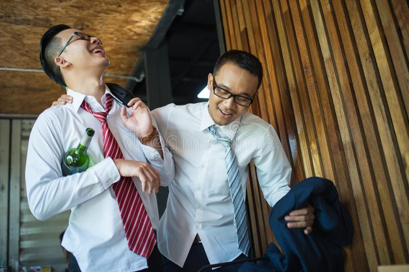 Zwei Geschäftsleute betrunken und lachen nach hartem Trinken im Restaurant, um den Erfolg der Arbeit zu feiern lizenzfreie stockfotos