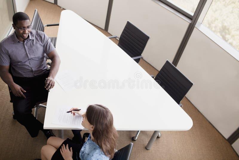 Zwei Geschäftsleute, die an einem Konferenztische sitzen und während eines Geschäftstreffens sich besprechen stockfotos