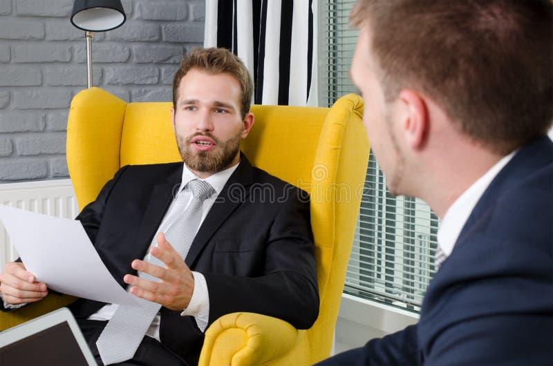 Zwei Geschäftsleute, die in einem modernen Büro sprechen stockfotografie
