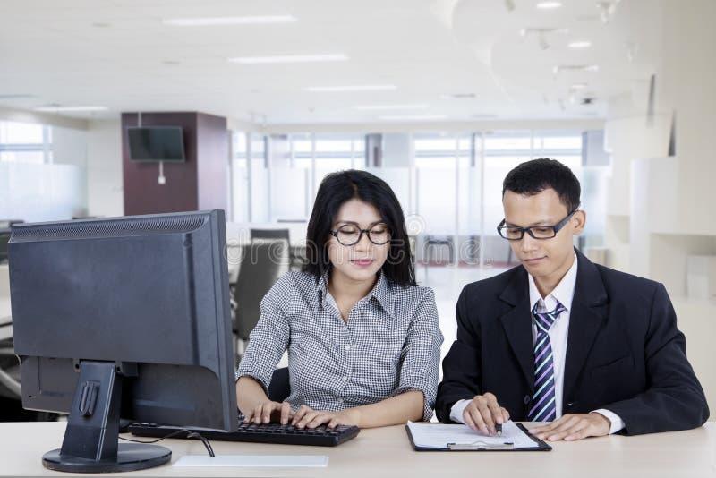 Zwei Geschäftsleute, die einen Computer im Büro verwenden stockbilder