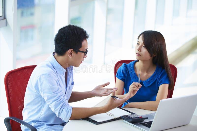Zwei Geschäftsleute, die im Büro sprechen lizenzfreies stockbild