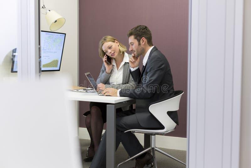 Zwei Geschäftsleute, die im Konferenzzimmer zusammenarbeiten stockfotos