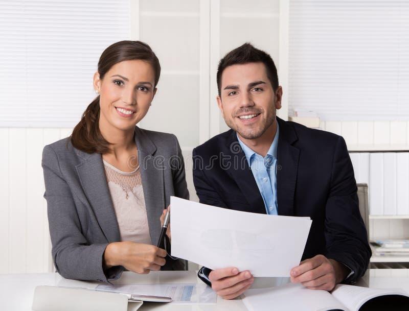Zwei Geschäftsleute, die im sprechenden und analysierenden Büro sitzen lizenzfreie stockfotografie
