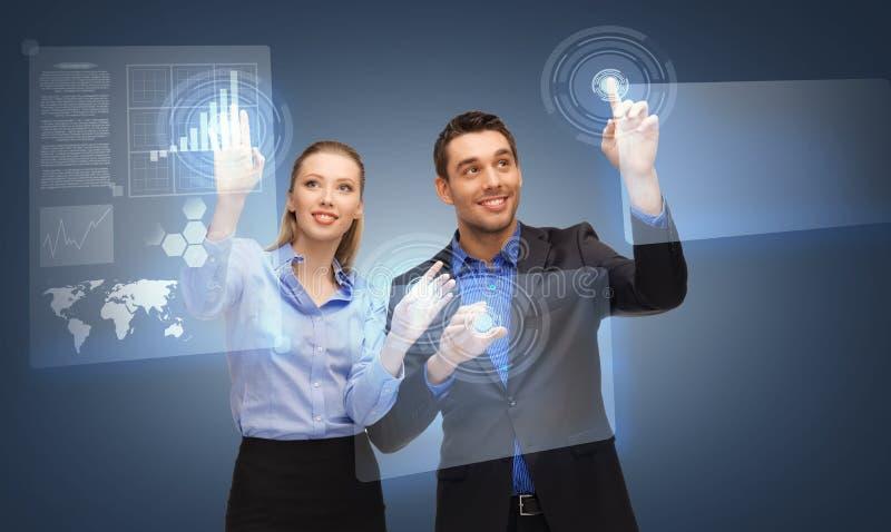 Zwei Geschäftsleute, die mit virtuellem Schirm arbeiten stockbild