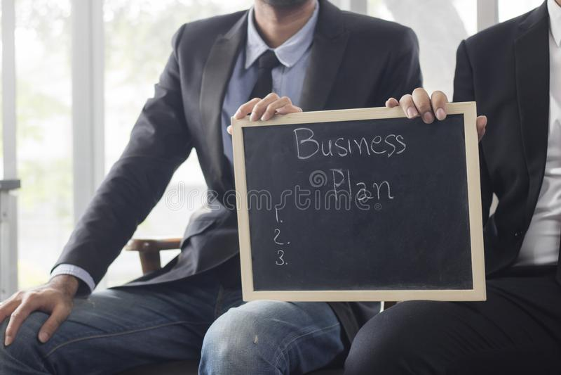 zwei Geschäftsleute, die schwarzes Brett mit Wortschrittplanung halten stockfoto
