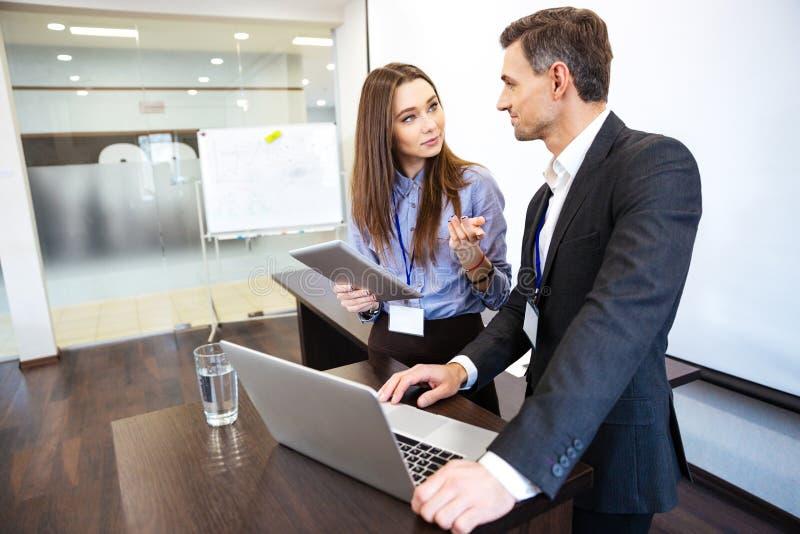 Zwei Geschäftsleute, die zusammen uing Laptop und Tablette bearbeiten stockbilder