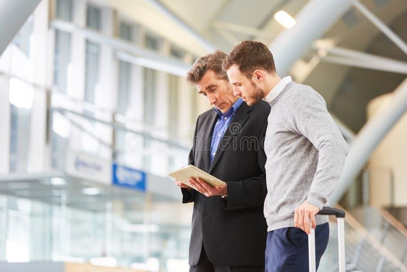 Zwei Geschäftsleute mit Tablet-Computer-Plandienstreise lizenzfreie stockfotografie