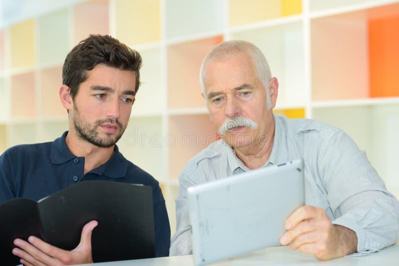 Zwei Geschäftsmänner in der Sitzung gesetzt im Büro lizenzfreie stockfotos