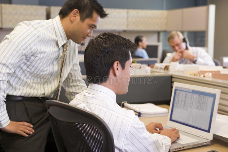 Zwei Geschäftsmänner in der Zelle, die Laptop betrachtet lizenzfreies stockfoto