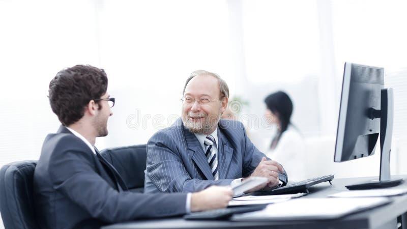 Zwei Geschäftsmänner, die Arbeit besprechen, gibt das Sitzen an ihrem Schreibtisch heraus lizenzfreies stockfoto