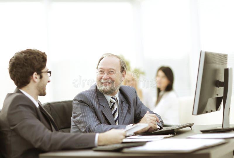 Zwei Geschäftsmänner, die Arbeit besprechen, gibt das Sitzen an ihrem Schreibtisch heraus stockfotos