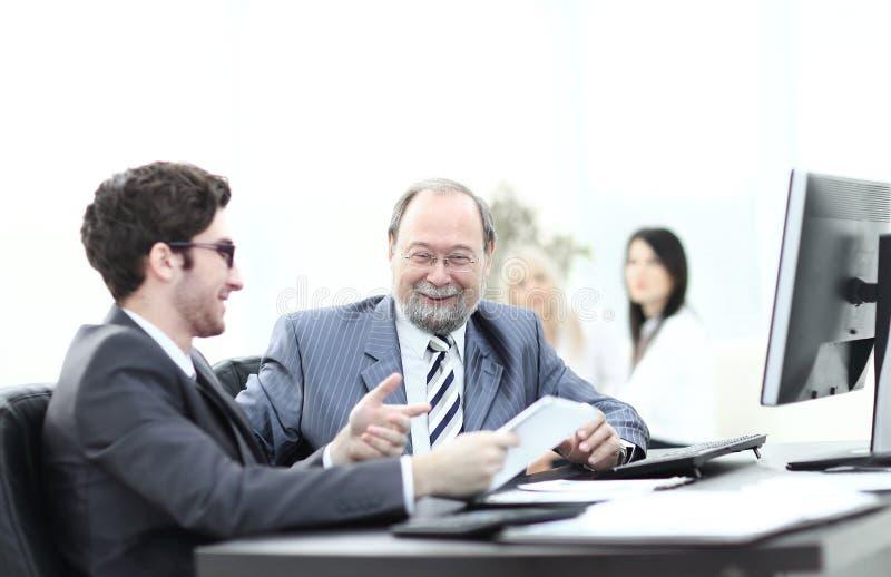 Zwei Geschäftsmänner, die Arbeit besprechen, gibt das Sitzen an ihrem Schreibtisch heraus stockfotografie