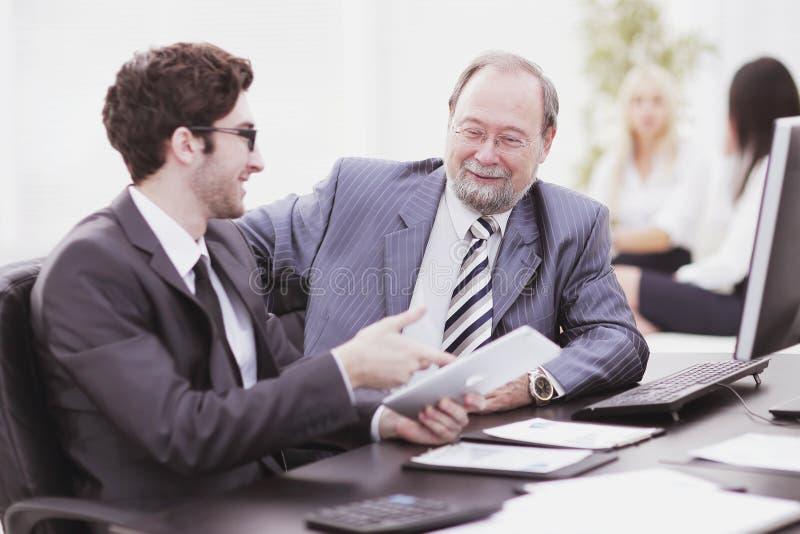 Zwei Geschäftsmänner, die Arbeit besprechen, gibt das Sitzen an ihrem Schreibtisch heraus stockbilder