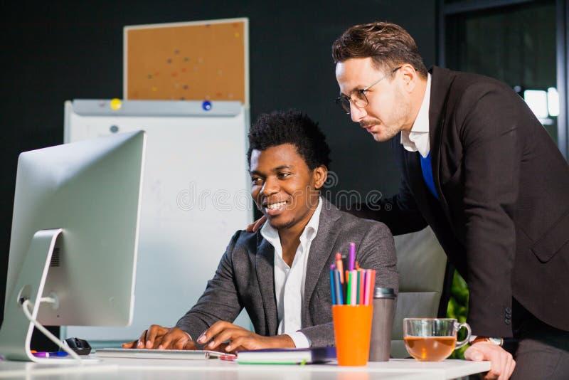 Zwei Geschäftsmänner, die Bildschirm, Teamwork-Konzept betrachten lizenzfreies stockfoto