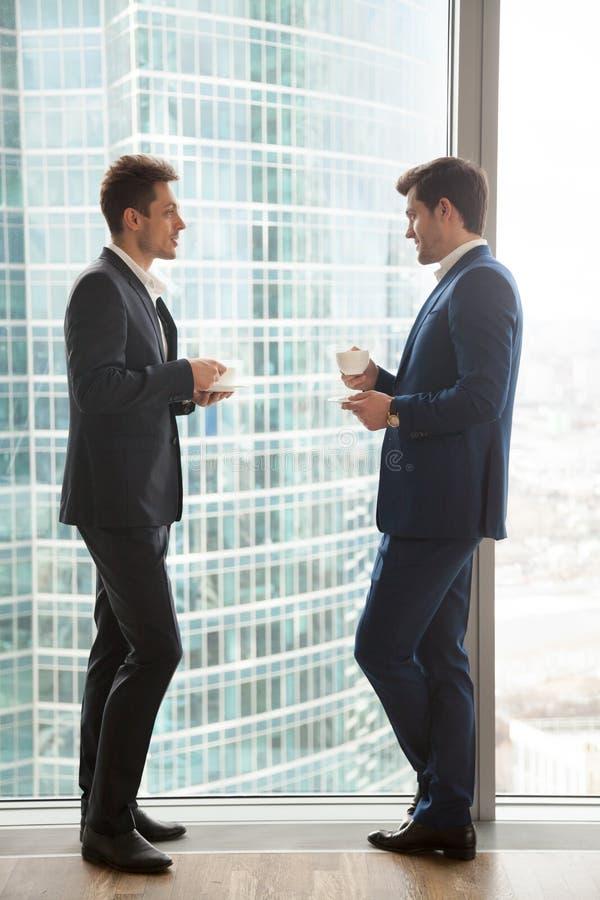 Zwei Geschäftsmänner, die, die Kaffeepause habend sprechen und stehen nahe voll lizenzfreie stockfotos
