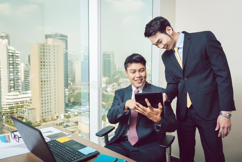 Zwei Geschäftsmänner, die digitale Tablette betrachten lizenzfreies stockbild