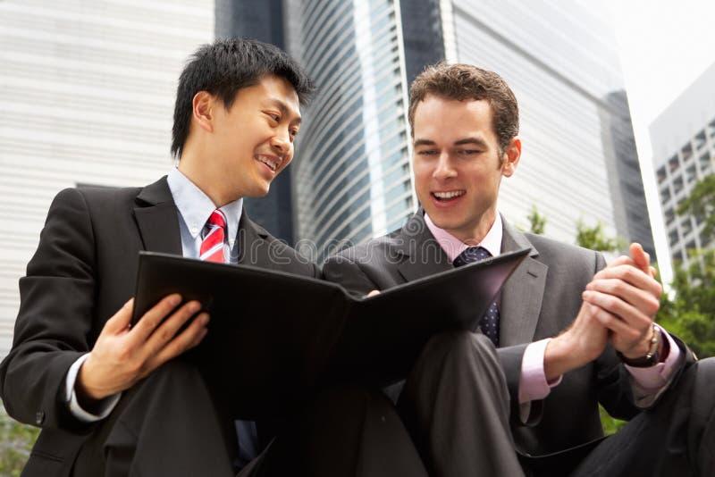Zwei Geschäftsmänner, die Dokument außerhalb des Büros behandeln stockbild
