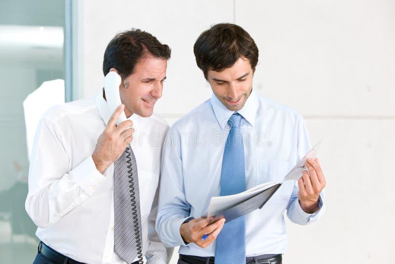 Zwei Geschäftsmänner, die Dokumente betrachten stockbild
