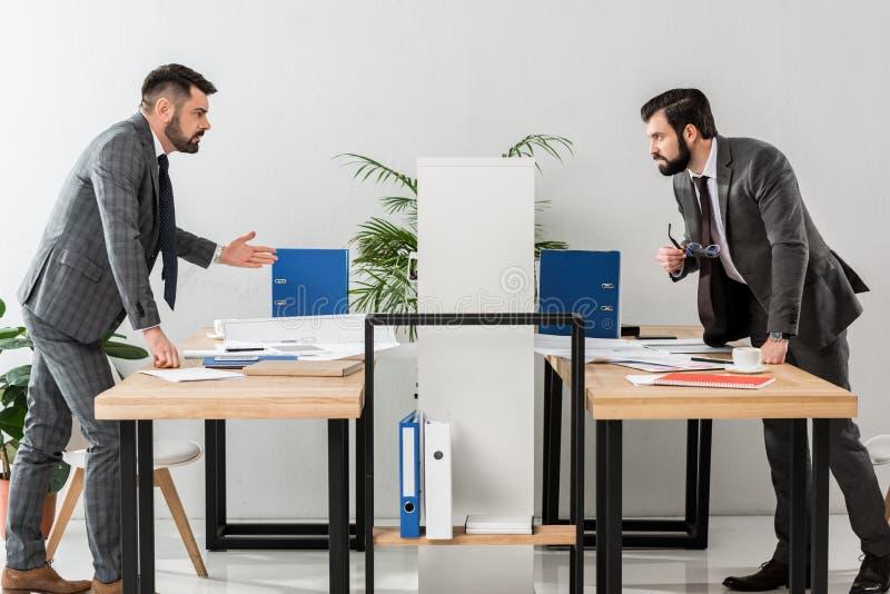 zwei Geschäftsmänner, die durch Fach streiten stockbild