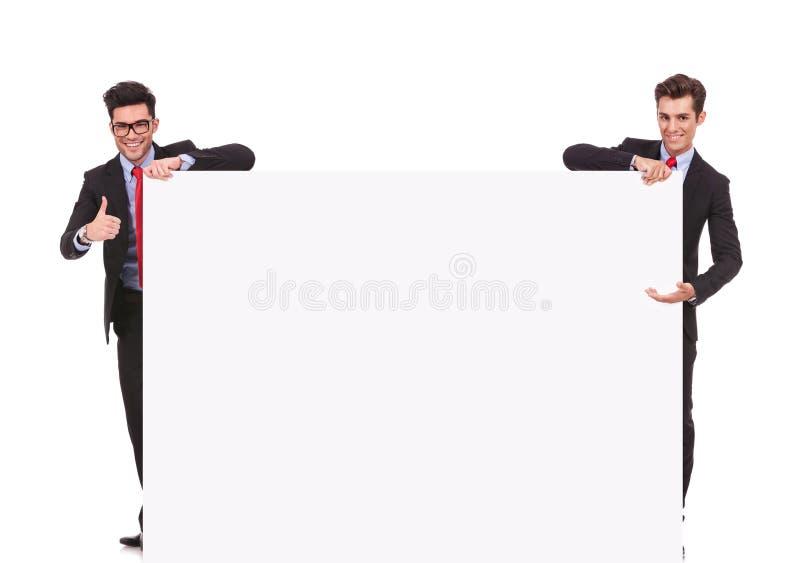 Zwei Geschäftsmänner, die ein großes leeres Zeichen anhalten stockbilder