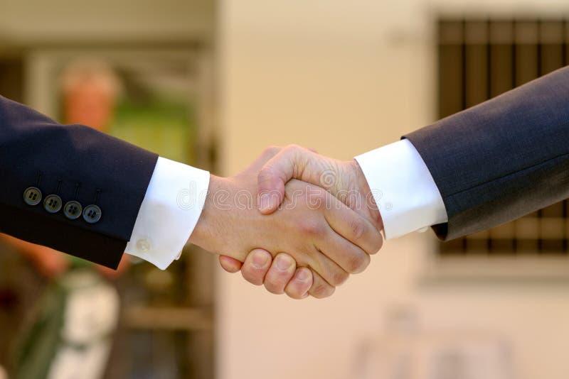 Zwei Geschäftsmänner, die einen festen Händedruck geben stockfotos