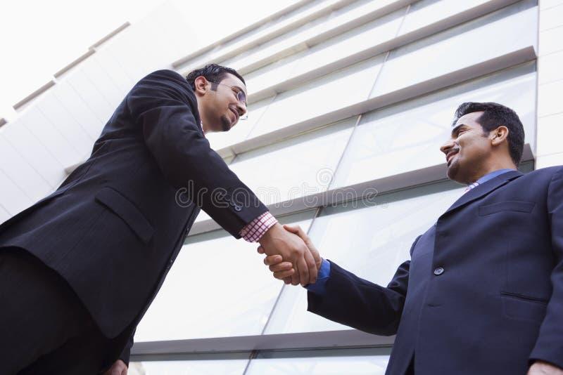 Zwei Geschäftsmänner, die Hände außerhalb des Bürobaus rütteln stockbild