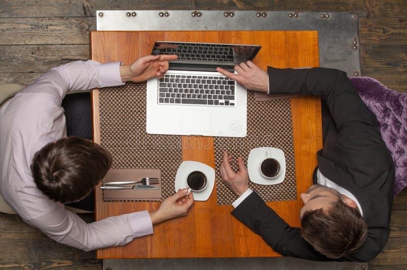 Zwei Geschäftsmänner, die im Café sitzen und Schirm betrachten lizenzfreie stockfotos
