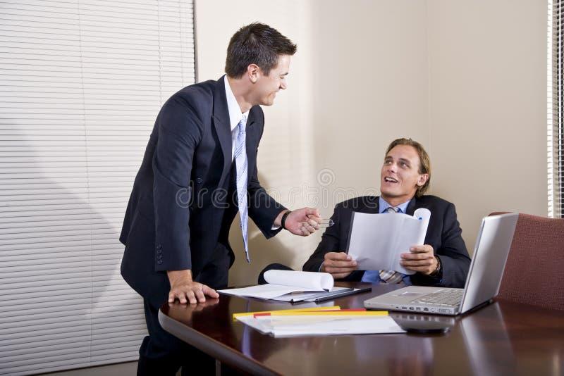 Zwei Geschäftsmänner, die im Sitzungssaal zusammenarbeiten stockbilder