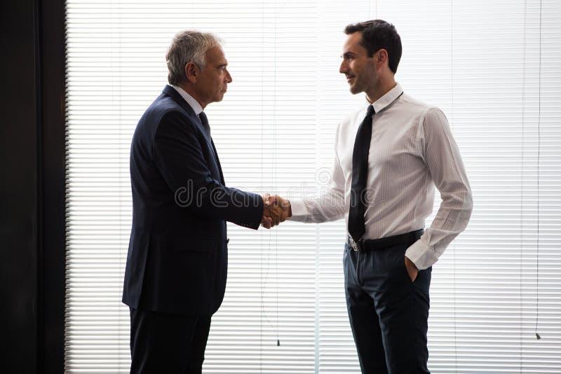 Zwei Geschäftsmänner, die oben stehen und Hände rütteln lizenzfreies stockbild