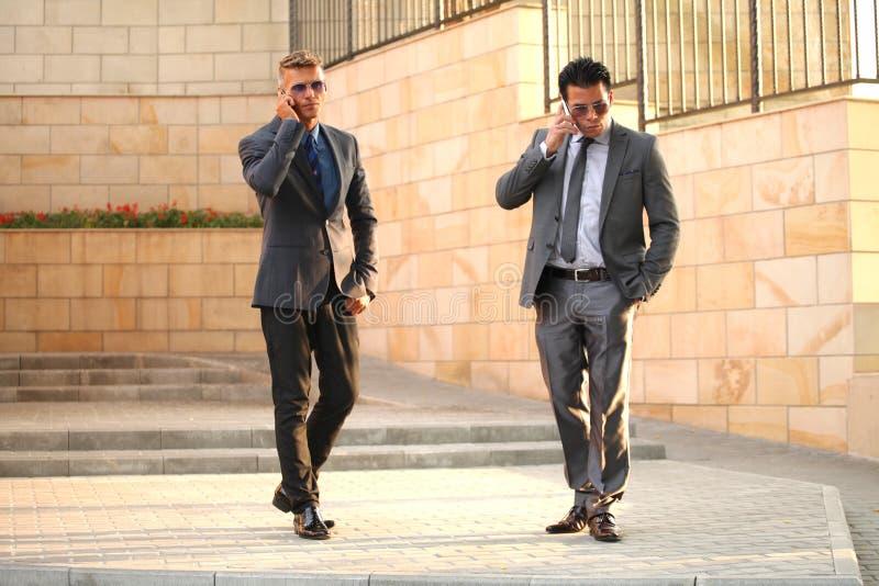 Zwei Geschäftsmänner mit Handys, nahe Wand, Sungl lizenzfreies stockfoto