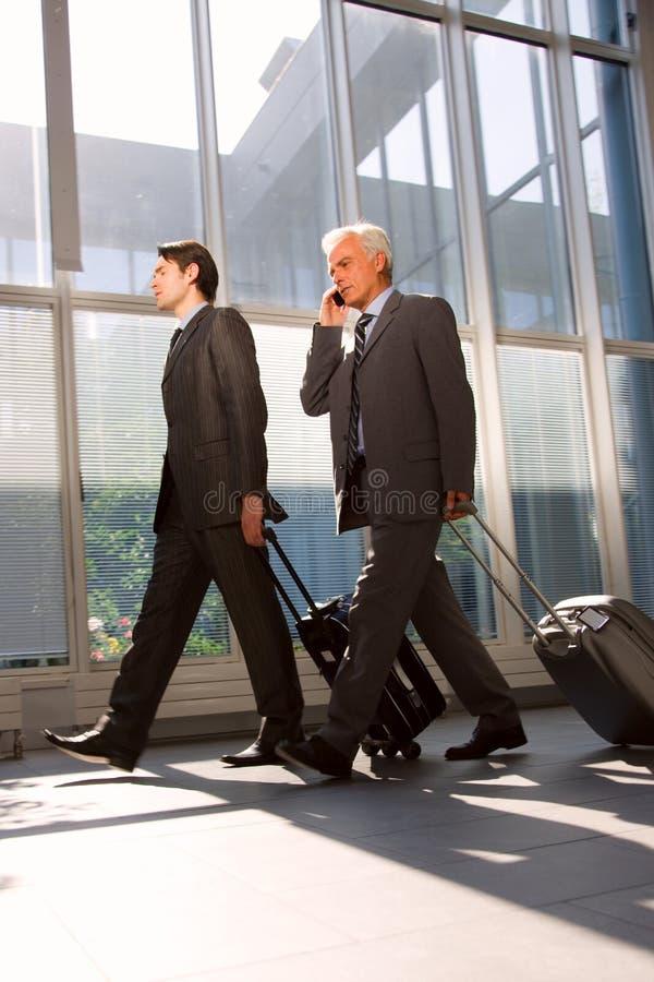 Zwei Geschäftsmänner mit Laufkatze lizenzfreie stockbilder