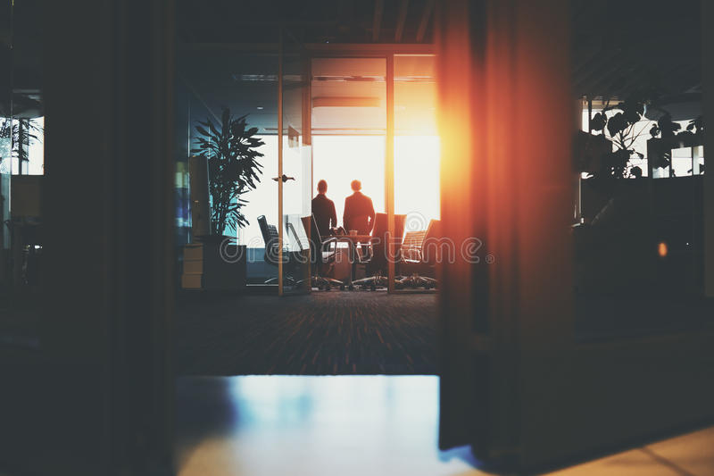 Zwei Geschäftsmänner nähern sich Fenster stockbild