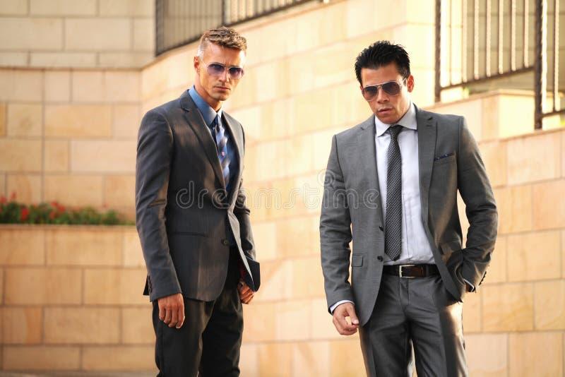 Zwei Geschäftsmänner nähern sich Wand, Sonnenbrille stockfotografie