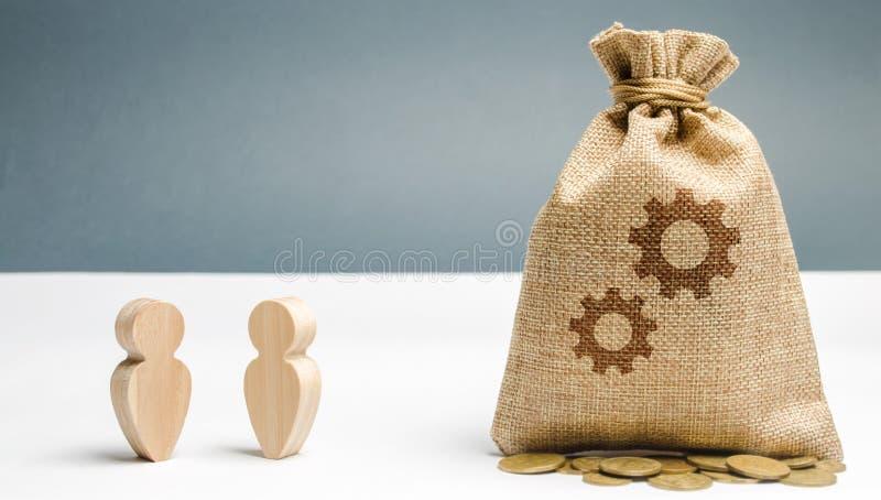Zwei Gesch?ftsm?nner stehen nahe der Tasche mit dem Bild von G?ngen Der Prozess des Lernens eines neuen Angestellten Anteilerfahr lizenzfreie stockfotos
