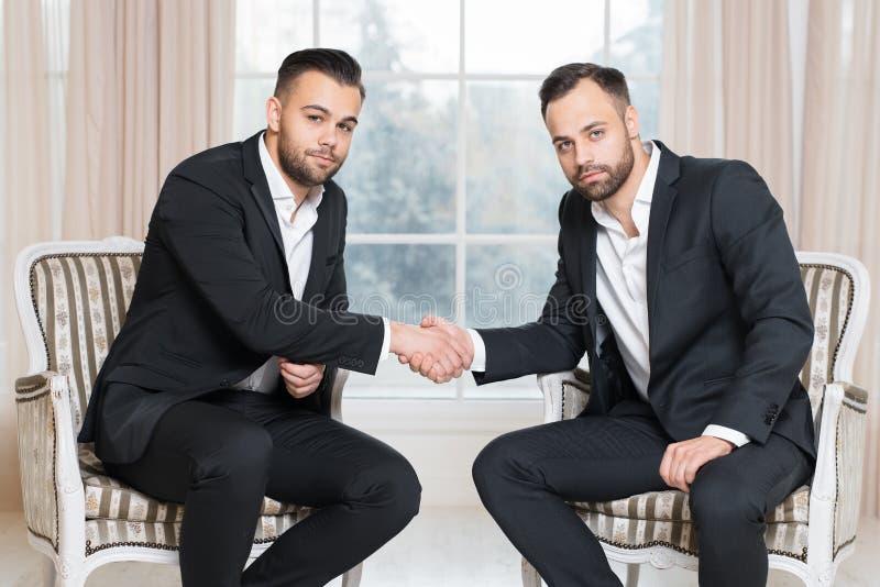 Zwei Geschäftsmänner, welche die Hände sitzen auf den Stühlen, gekleidet in den Klagen, über Hintergrund des Fensters rütteln lizenzfreie stockfotos