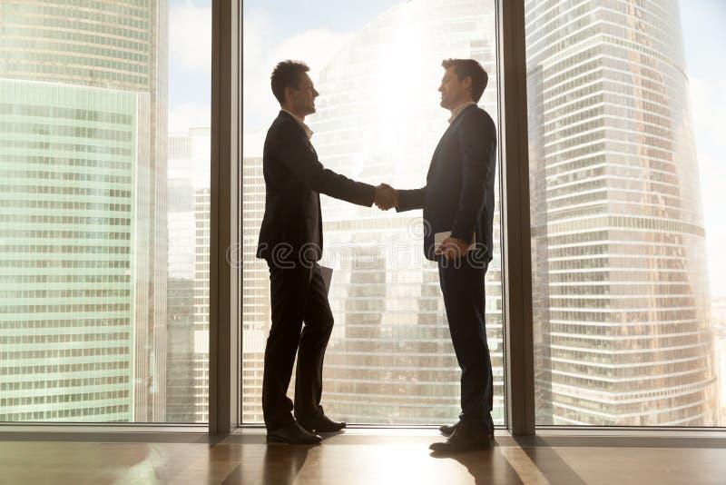 Zwei Geschäftsmänner, welche die Hände stehen nahe großem Fenster, städtisches Ci rütteln lizenzfreie stockfotografie