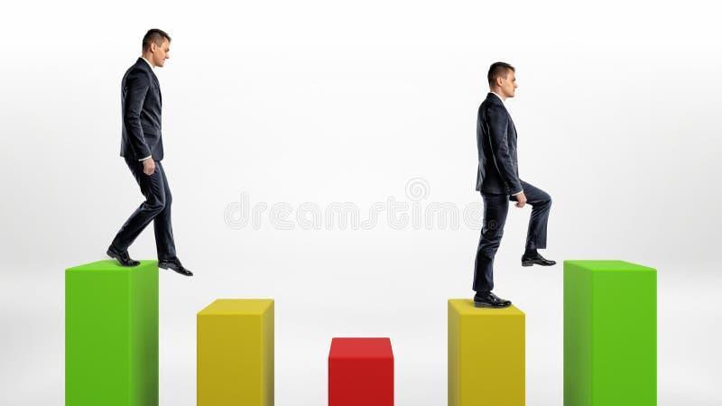 Zwei Geschäftsmann- auf weißem Hintergrund steigernd und unten grün, Gelbe und Grünestatistikspalten lizenzfreie stockfotografie