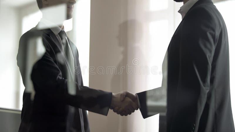 Zwei Gesch?ftsm?nner, die miteinander H?nde, Abkommen, Ansicht durch Glas best?tigend r?tteln lizenzfreies stockfoto