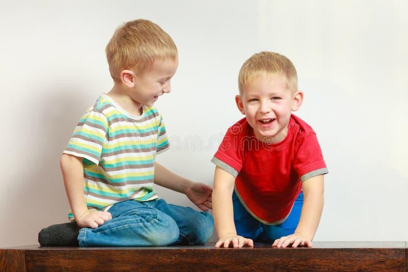 Zwei Geschwister der kleinen Jungen, die zusammen auf Tabelle spielen stockbild