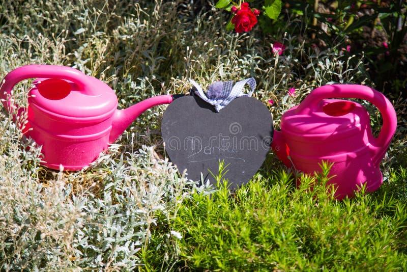Zwei Gießkannen mit einem Herzen im Garten, Hobbygärtner stockfoto