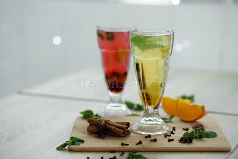 Zwei Gläser mit farbigen heißen Getränken, von denen Dampf kommt Winter heiße Saison-vitemin Getränke stockfoto