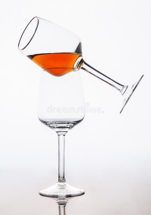 Zwei Gläser zum Nachtisch Wein Ein Glas Weinbalancen auf dem anderen Auf einem weißen Hintergrund Getrennt lizenzfreie stockfotografie