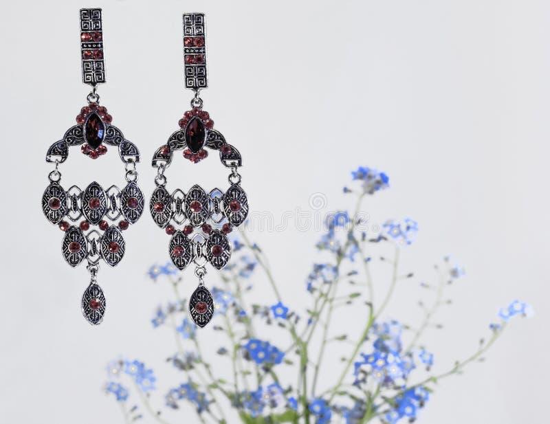 Zwei glänzende silberne Ohrringe mit hellen roten Steinen und ein Blumenstrauß von Vergissmeinnichten lizenzfreie stockfotos
