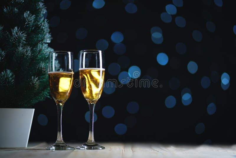 Zwei Gläser Champagne und kleines Weihnachtsbaum-dunkles Glühen Ligh lizenzfreie stockbilder