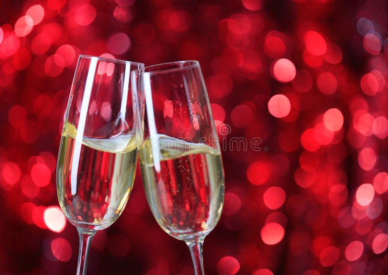 Zwei Gläser Champagner gegen roten Hintergrund mit Scheinen Sehr flache Schärfentiefe gegen roten Hintergrund mit Scheinen lizenzfreie stockfotografie