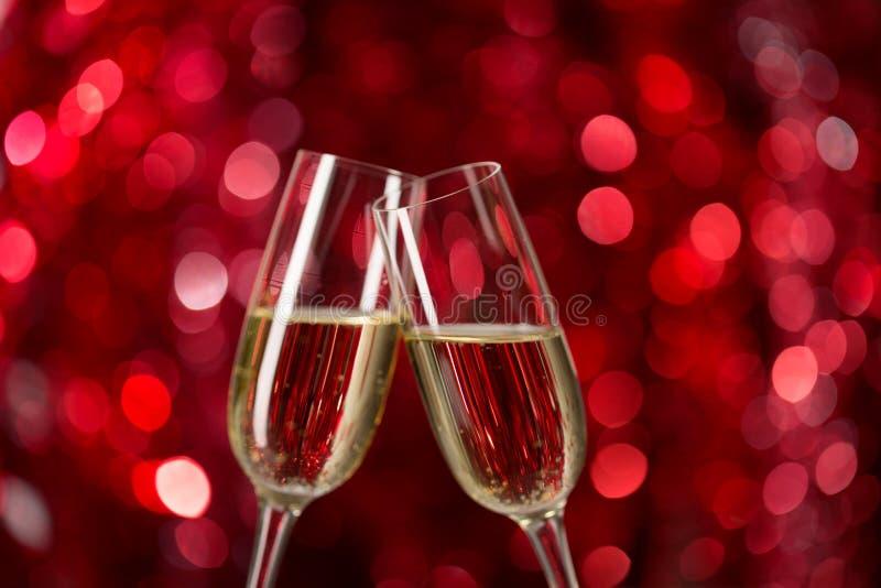 Zwei Gläser Champagner gegen roten Hintergrund mit Scheinen Sehr flache Schärfentiefe Selektiver Fokus lizenzfreies stockbild