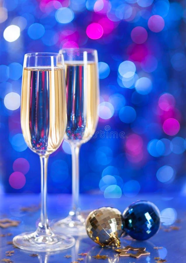 Zwei Gläser Champagner mit einem Weihnachtsdekor im Hintergrund sehr flache Schärfentiefe, Fokus auf nahem Glas lizenzfreies stockbild
