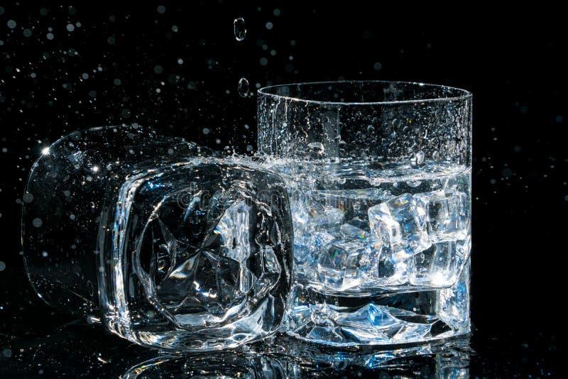 Zwei Gläser der hohen Qualität Whisky, man liegt auf Seite und anderes mit Eiswürfeln und -wasser spritzt stockbilder